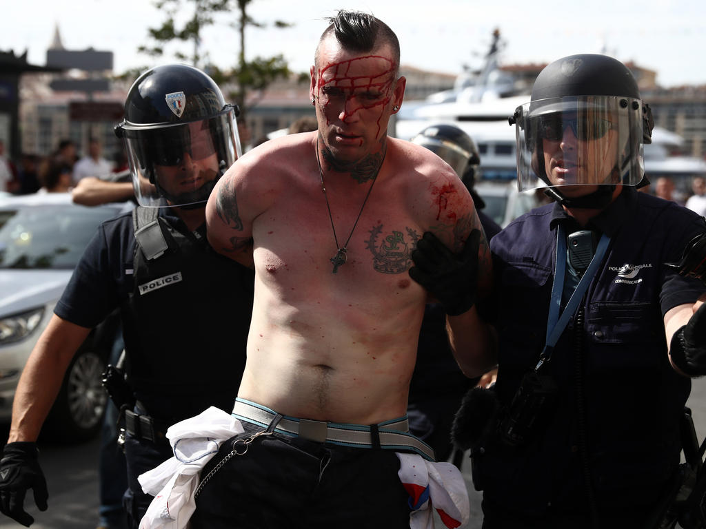 MARSEILLE, FRANCE - JUNE 11: An injured Austria fan is arrested after clashing with police ahead of the game against Russia later today on June 11, 2016 in Marseille, France. Football fans from around Europe have descended on France for the UEFA Euro 2016 football tournament. (Photo by Carl Court/Getty Images)