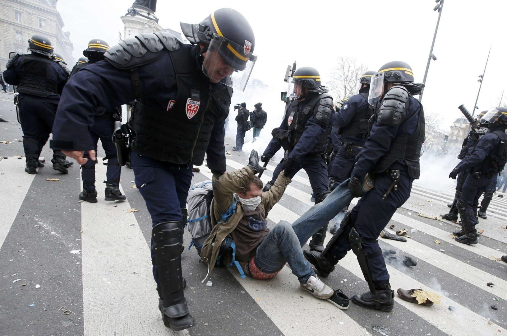 French CRS riot police apprehend a demonstrator during clashes near the Place de la Republique after the cancellation of a planned climate march following shootings in the French capital, ahead of the World Climate Change Conference 2015 (COP21), in Paris, France, November 29, 2015.          REUTERS/Eric Gaillard   TPX IMAGES OF THE DAY