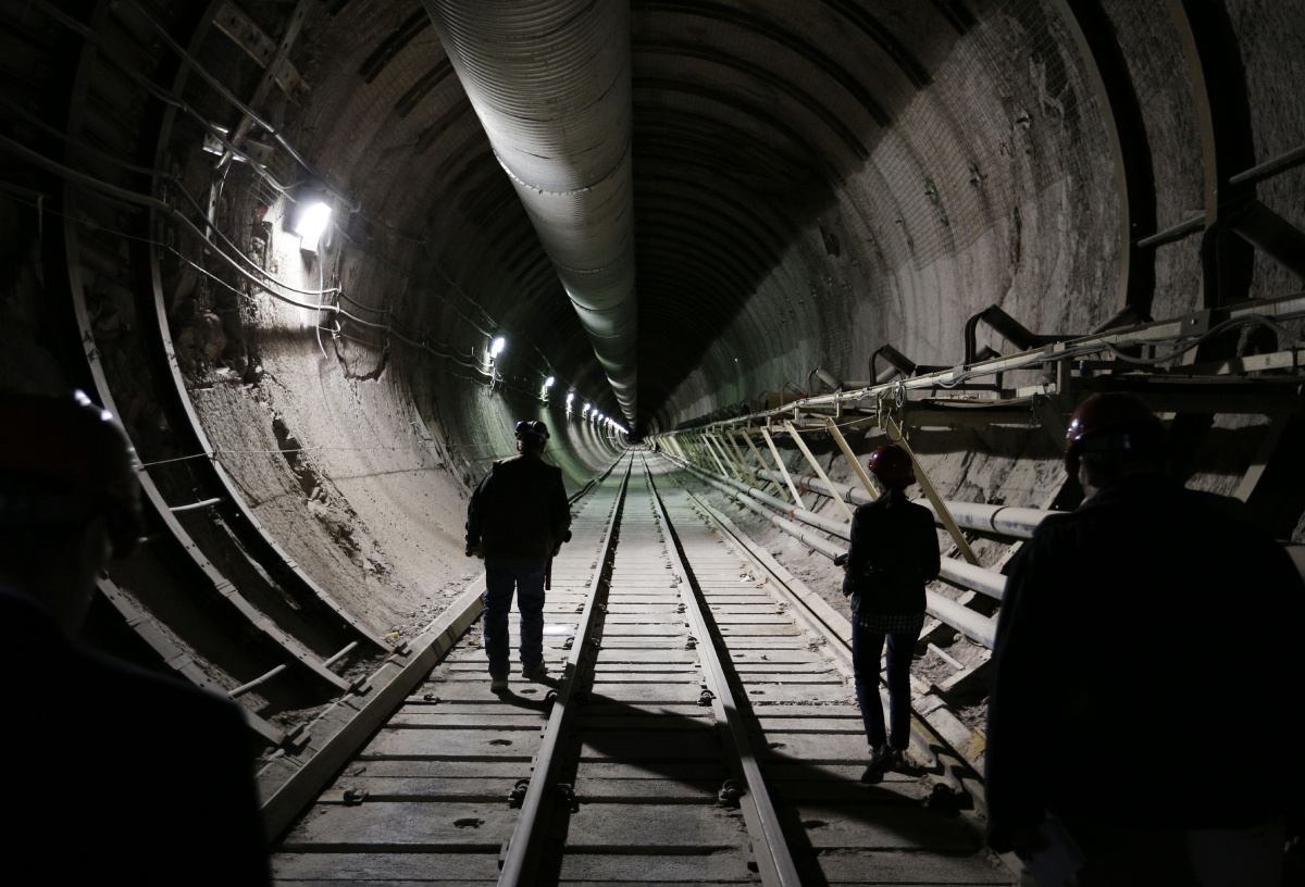 People walk in a tunnel through Yucca Mountain during a congressional tour Thursday, April 9, 2015, near Mercury, Nev. Several members of Congress toured the proposed radioactive waste dump 90 miles northwest of Las Vegas. (AP Photo/John Locher)