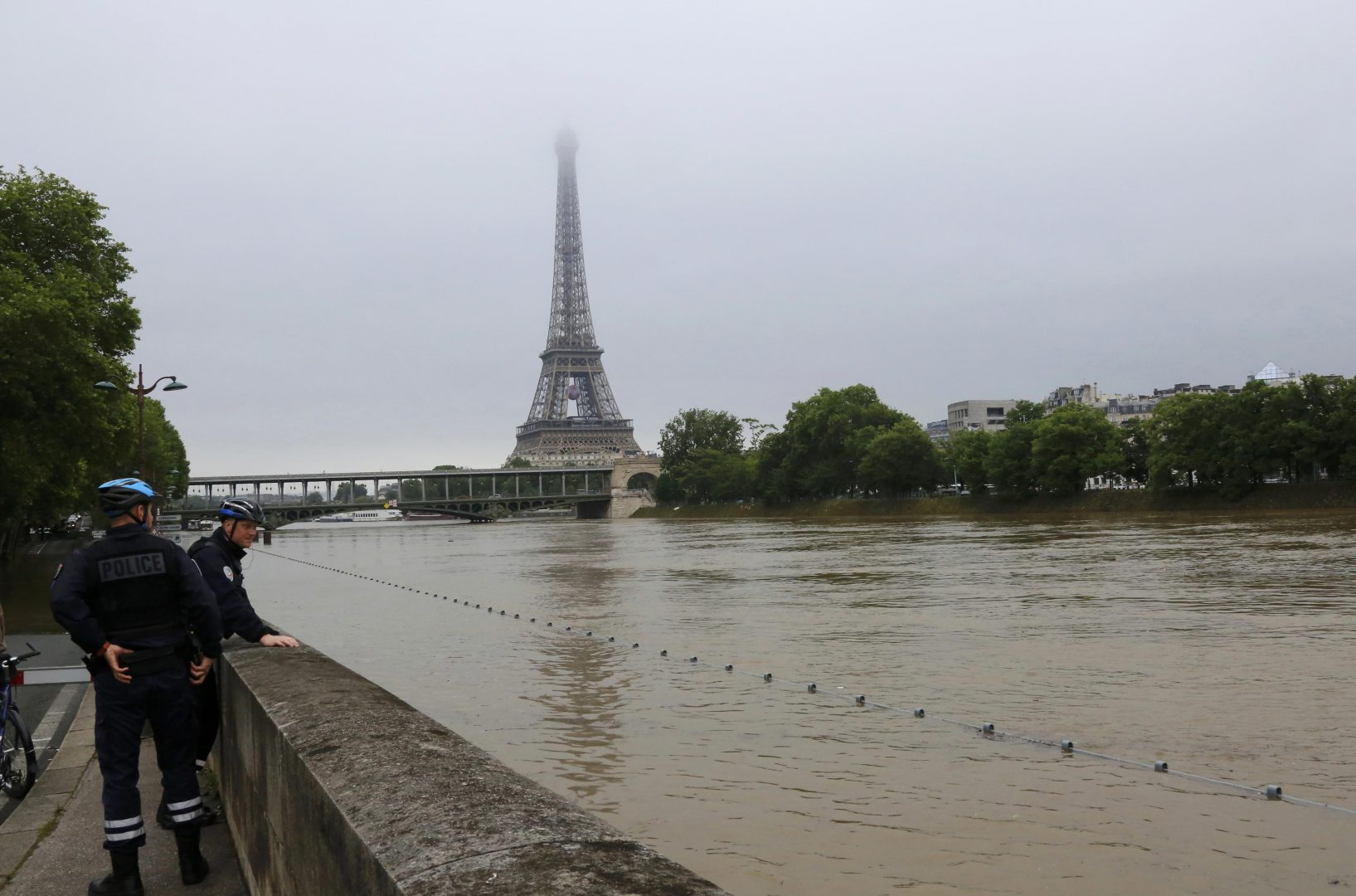 French police stop to look at flooding on the banks of the Seine River near the Eiffel Tower after days of heavy rainfall in Paris, France, June 2, 2016. REUTERS/Jacky Naegelen