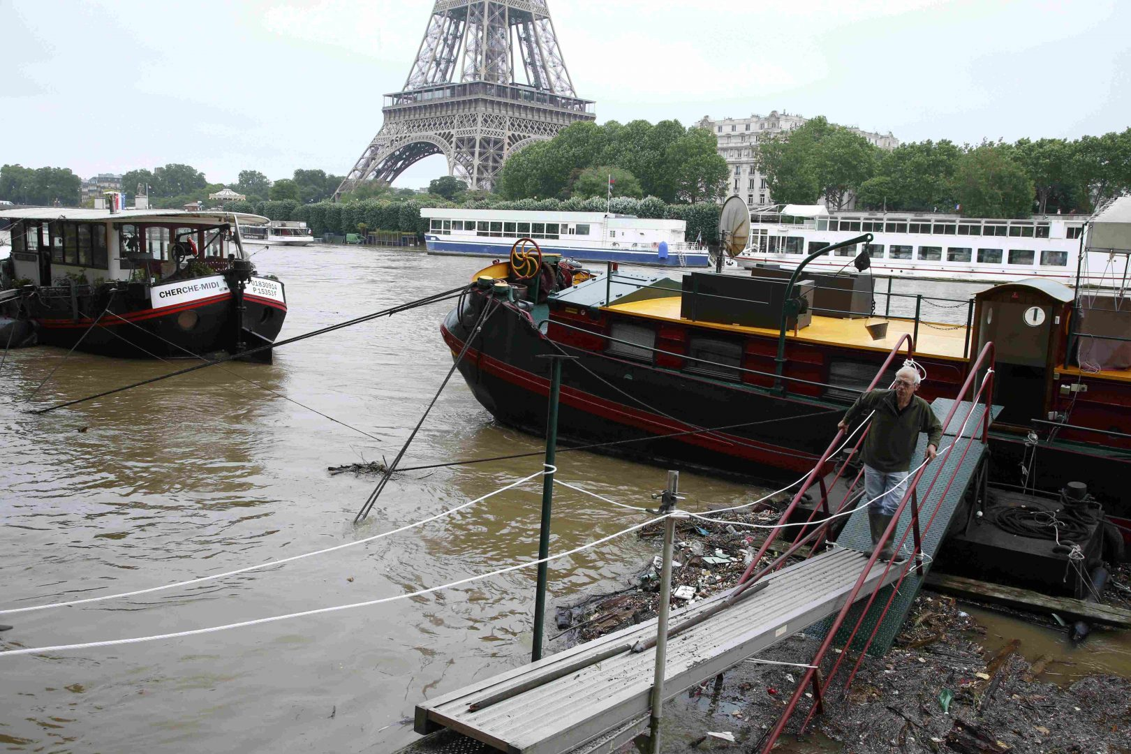 A man uses a footbridge as he leaves his houseboat moored near the Eiffel tower during flooding on the banks of the Seine River in Paris, France, after days of almost non-stop rain caused flooding in the country, June 2, 2016. REUTERS/Pascal Rossignol