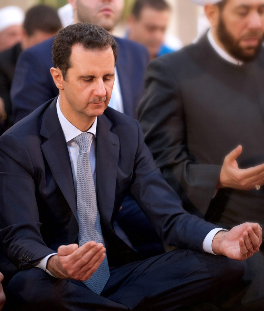 "A picture released by Syria's official news agency SANA shows Syrian President Bashar al-Assad peforming the morning prayer of the Muslim holiday of Eid al-Adha at the Al-Adel mosque in Damascus on September 24, 2015, in a rare public appearance for the embattled regime head. Assad attended the prayer of the Muslilm holiday of sacrifice along with state and ruling Baath party officials as well as a number of Muslim religious leaders and civilians, Syria's official news agency SANA reported. AFP PHOTO / HO / SANA == RESTRICTED TO EDITORIAL USE - MANDATORY CREDIT ""AFP PHOTO / HO / SANA"" - NO MARKETING NO ADVERTISING CAMPAIGNS - DISTRIBUTED AS A SERVICE TO CLIENTS =="