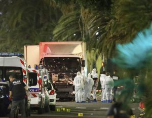 French police forces and forensic officers stand next to a truck that ran into a crowd celebrating the Bastille Day national holiday on the Promenade des Anglais killing at least 60 people in Nice