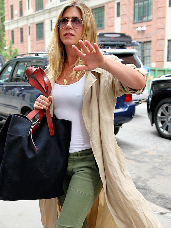 Actress Jennifer Aniston, wearing a flowing trench coat, green pants and sandals, returns home in New York City on June 16, 2016. Jennifer almost gets her toe crushed by her bodyguard! Pictured: Jennifer Aniston Ref: SPL1303233 160616 Picture by: Christopher Peterson/Splash News Splash News and Pictures Los Angeles:310-821-2666 New York:212-619-2666 London:870-934-2666 photodesk@splashnews.com