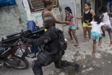 "Special Police Operations Battalion (BOPE) officer takes position while residents run for cover during an operation in the Mare slum complex, ahead of its ""pacification,"" in Rio de Janeiro, Brazil, Wednesday, March 26, 2014. Elite federal police and army troops will be sent to the city to help quell a wave of violence in so-called ""pacified"" slums. Recent attacks on police bases in the favelas is raising concerns about an ambitious security program that began in 2008, in part to secure the city ahead of this year's World Cup and the 2016 Olympics. (AP Photo/Silvia Izquierdo)"