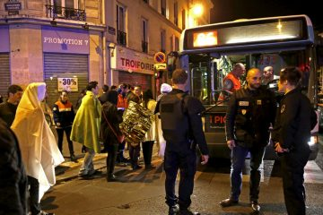 French police stand near people warming up on a street before being evacuated by bus near the Bataclan concert hall following fatal attacks in Paris, France, November 14, 2015. Gunmen and bombers attacked busy restaurants, bars and a concert hall at locations around Paris on Friday evening, killing dozens of people in what a shaken French President described as an unprecedented terrorist attack   REUTERS/Philippe Wojazer