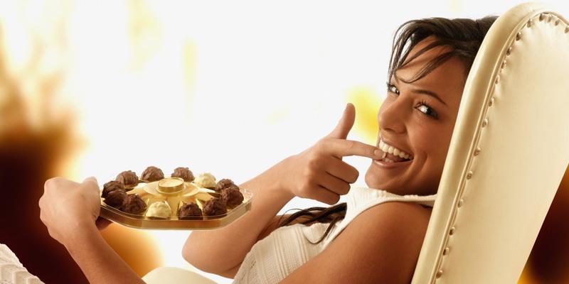 Hispanic woman eating chocolate