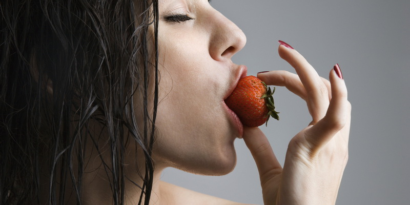 Topless caucasian woman biting a strawberry.