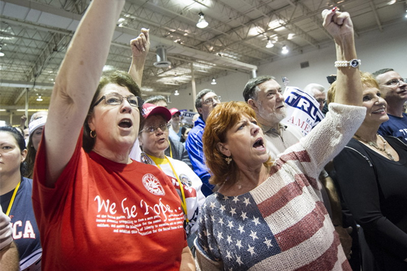 Supporters Claudia Sanchez, left, and Irish Lyn Murphy, right, both from Woodstock, Ga., cheer on Republican presidential candidate Donald Trump during a campaign rally at the North Atlanta Trade Center, Saturday, Oct., 10, 2015, in Norcross, Ga. (AP Photo/John Amis)